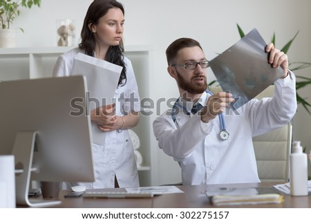Doctors discussing intestines xray at medical office - stock photo