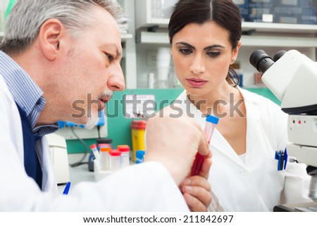 Doctors examining a blood sample in a laboratory - stock photo