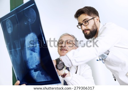 doctors examining an X-ray of a woman's body - stock photo