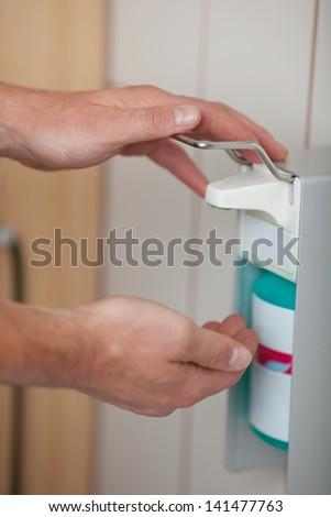 Doctors hands using sanitizer dispenser in washroom - stock photo