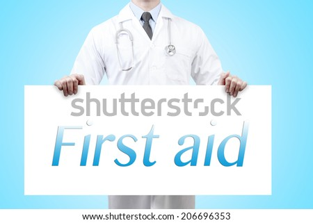 doctors holding a white banner have words first aid  - stock photo