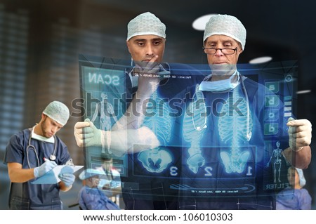 Doctors in a medical facility looking at digital screen - stock photo