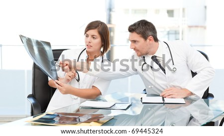 Doctors looking at  x-ray  in their office - stock photo