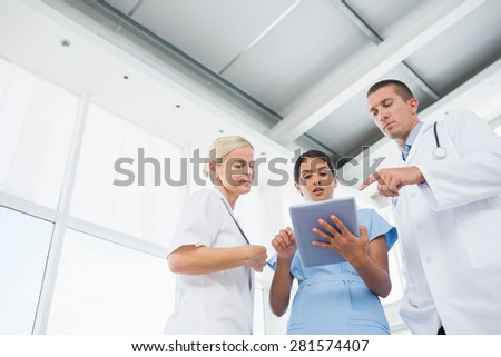 Doctors looking together at tablet in medical office - stock photo
