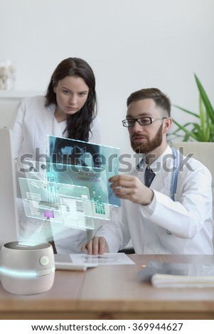 Doctors looking x-ray of his patient at his office. Using futuristic virtual computer interface - stock photo