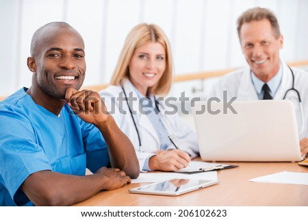 Doctors meeting. Three cheerful doctors sitting together at the table and smiling at camera - stock photo