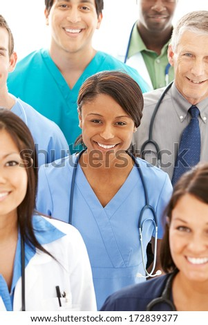 Doctors: Pretty Doctor in Middle of Group of Professionals - stock photo