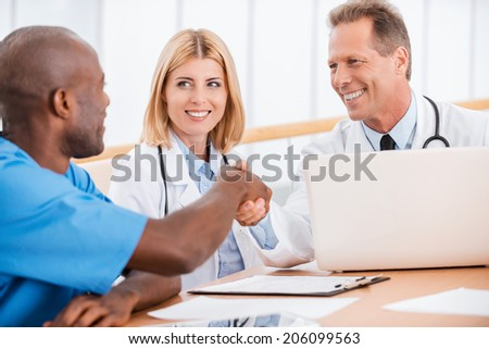 Doctors shaking hands. Two cheerful doctors shaking hands while sitting together with female doctor - stock photo