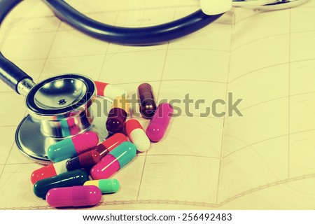 Doctors Stethoscope on a blank notepad with colorful  pills for medical concept in vintage style. - stock photo