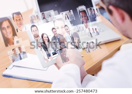 Doctors using laptop and digital tablet in meeting against portrait of a positive team sitting at a table - stock photo