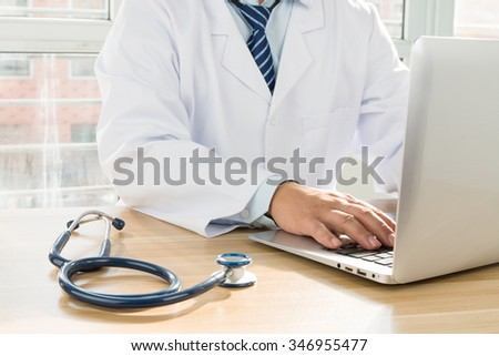 Doctors using laptop at work - stock photo
