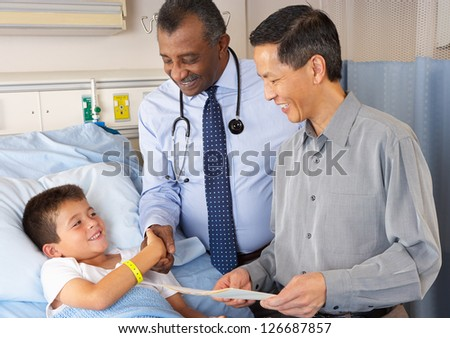 Doctors Visiting Child Patient On Ward - stock photo