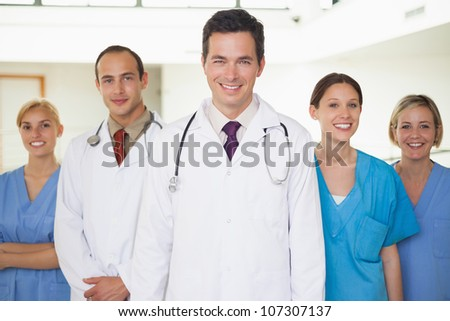 Doctors with nurses looking at camera in hospital corridor - stock photo