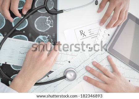 Doctors working at the desk in the hospital - stock photo
