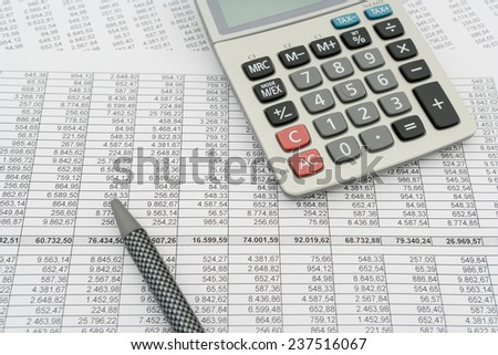 document with numbers in several columns, calculator and pen - stock photo