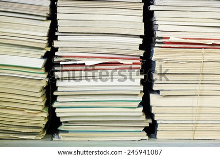 documents stacked on the shelf of an archive - stock photo