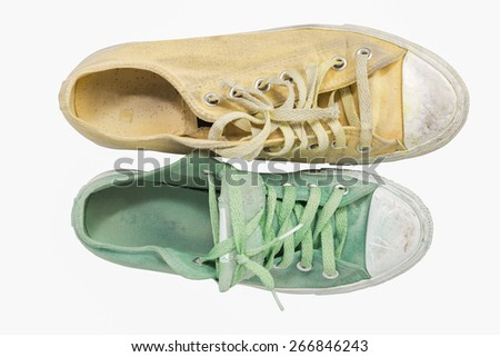 Does not match yellowand green  sneakers on white background - stock photo