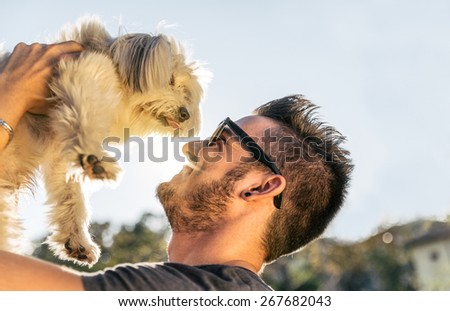 Dog and his owner - Cool dog and young man having fun in a park - Concepts of friendship,pets,togetherness - stock photo