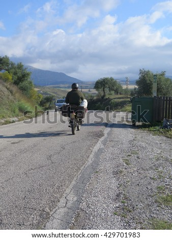Dog being transported in pannier on moped in Andalusia - stock photo