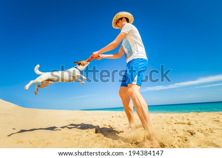 dog catching a red frisbee with owner spinning around - stock photo
