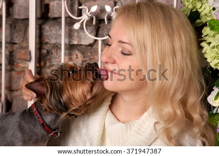 Dog kissing and licking a young woman. Pets love. - stock photo