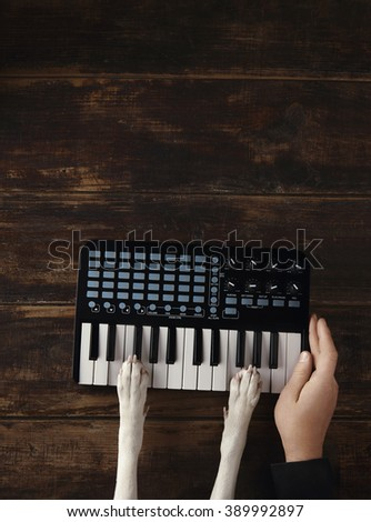 Dog paws on small wireless portable midi piano keyboard mixer top view. Owner man hand lies near.