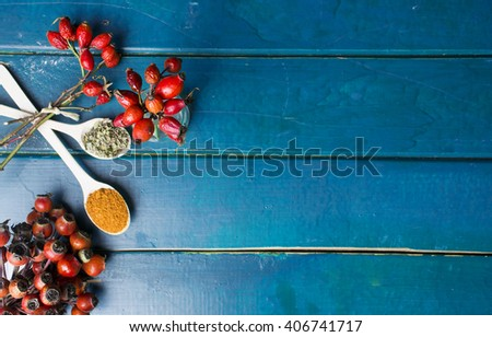 Dog roses and essential oil, bunch of dog rose,Different types Rosa canina hips and hawthorn, dry goji berries, briar powder in wooden spoon. chinese herbal medicine selection in wooden - stock photo
