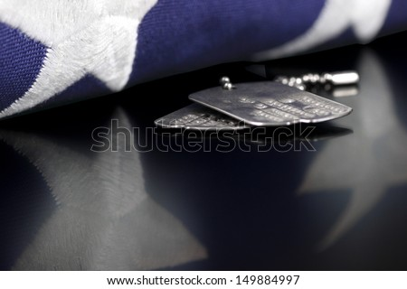 Dog tags or ID tags, once worn by a military veteran with a folded US flag - stock photo