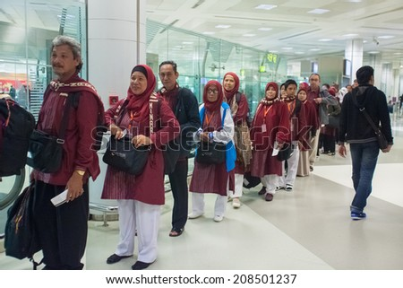 DOHA, QATAR - FEBRUARY 18, 2014: Passengers wait in check-in line at Doha International Airport, the only commercial airport in Qatar. - stock photo