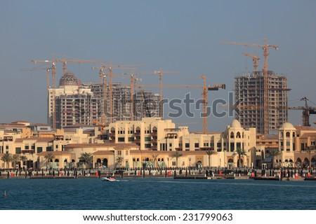 DOHA, QATAR - JAN 8: Construction cranes in Porto Arabia. January 8, 2012 in Doha, Qatar, Middle East - stock photo