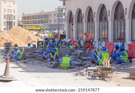 DOHA, QATAR - MARCH 8, 2015: Asian labourers at work removing a paved area from Souq Waqif, a popular tourist destination in Doha - stock photo