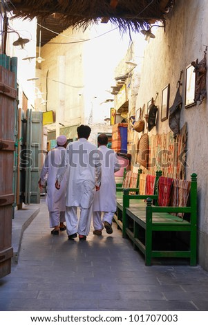 Doha, Qatar - Three man in local traditional dress in Souk Waqif - stock photo