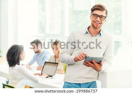 Doing business with a smile. Happy young man holding digital tablet and looking at camerawhile his colleagues working in the background - stock photo