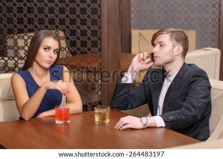 Doing business. Young man talking over the phone while his girlfriend looks bored and disappointed as he doesnt pay attention to her - stock photo