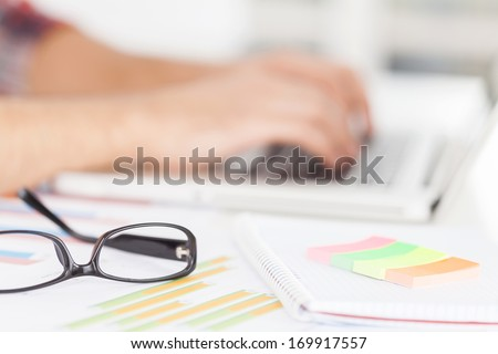 Doing creative work. Cropped image of man working on laptop while sitting at his working place - stock photo