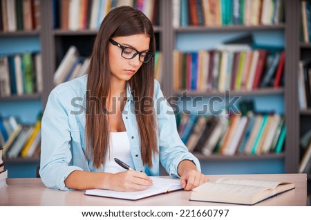 Doing her homework. Young woman writing something in her note pad and reading book while sitting at the desk in the library - stock photo
