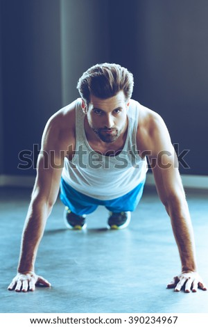 Doing push-up at gym. Front view of young handsome man in sportswear doing push-up and looking at camera at gym - stock photo
