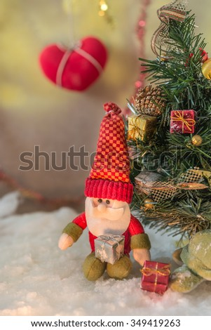 doll of santa claus with christmas tree in snow,