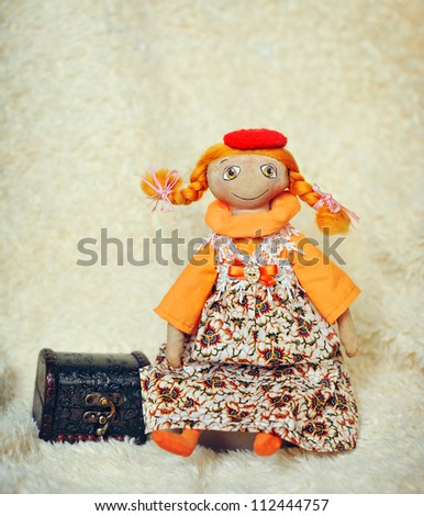 doll with red hair to a red cap with a chest - stock photo