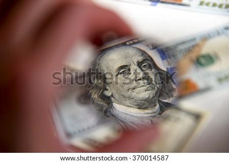 Dollar banknote through magnifying lens  - stock photo