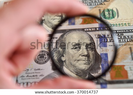 Dollar banknote through magnifying lens (corruption, lobbying, inflation, financial secrecy - concept). - stock photo