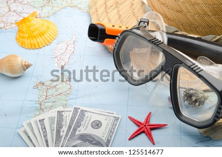 Dollar banknotes on a map with snorkel mask - stock photo