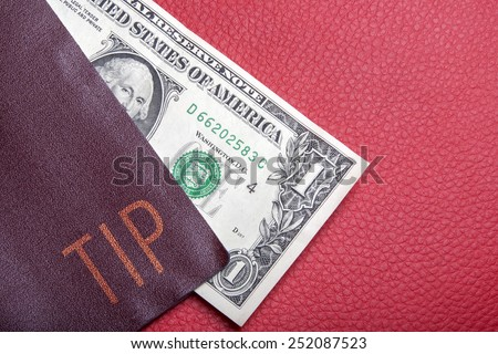Dollar bill lying in the cover with the inscription: Tip - stock photo