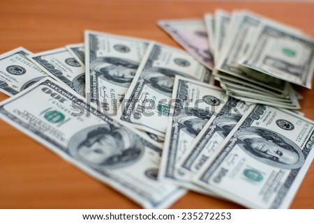 Dollar bills are in a chaotic manner on the table - stock photo