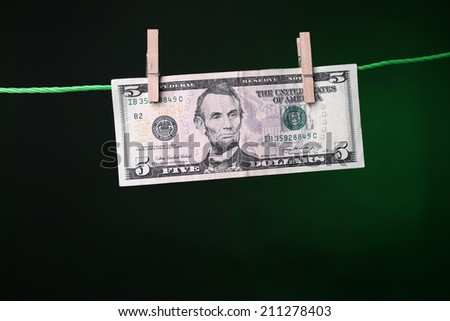 Dollar bills hanging on rope attached with clothes pins. Money-laundering concept. On dark color background - stock photo