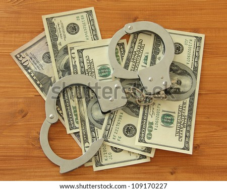 Dollar bills with handcuffs on a wooden desk - stock photo
