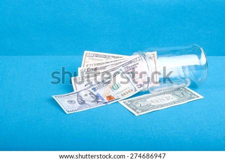 Dollar bills woken from a glass jar near  dollar, side view, blue background - stock photo