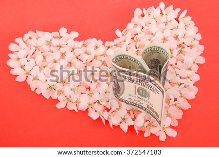 Dollar from heart on heart made of flowers. On red background. - stock photo