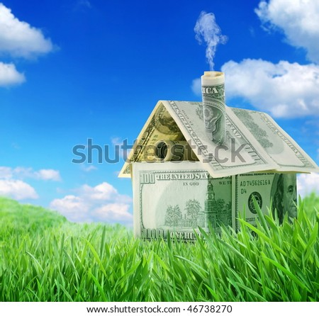 Dollar house in a green grass field over blue sky - stock photo