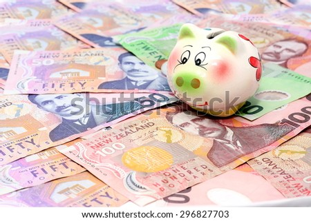 Dollar notes in New Zealand currency $100 $50 $20 and piggy bank  - stock photo